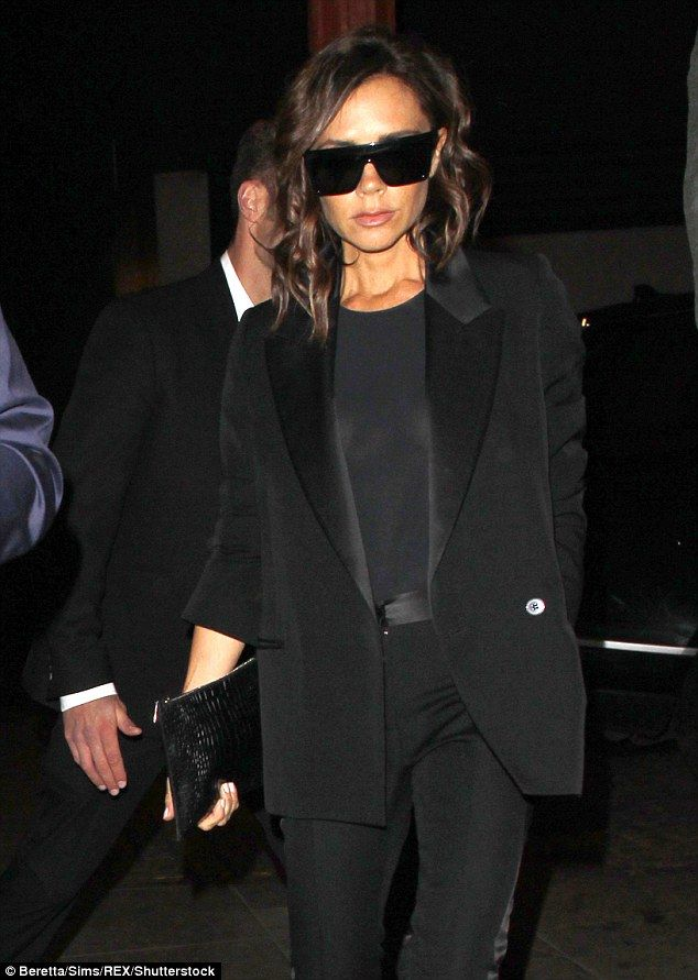 Back to black: Victoria Beckham looked sombre in her tailored black suit jacket and sheer top as she arrived at Dave Gardner's birthday party in London on Friday night