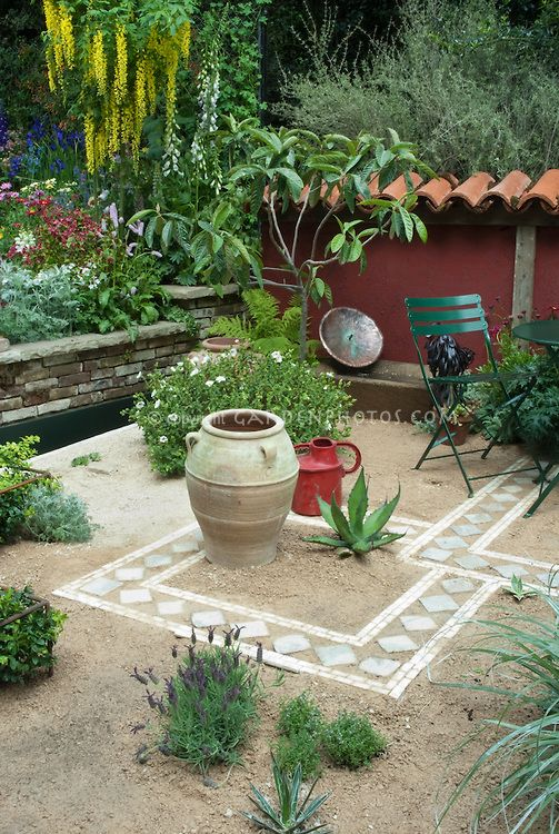 Creating an outdoor patio with sand and tiles, using water-wise succulent plants and drought tolerant herbs such as lavender Lavandula, with raised beds of perennial flowers, Laburnum tree in bloom, low wall, patio furniture, ornamental urn
