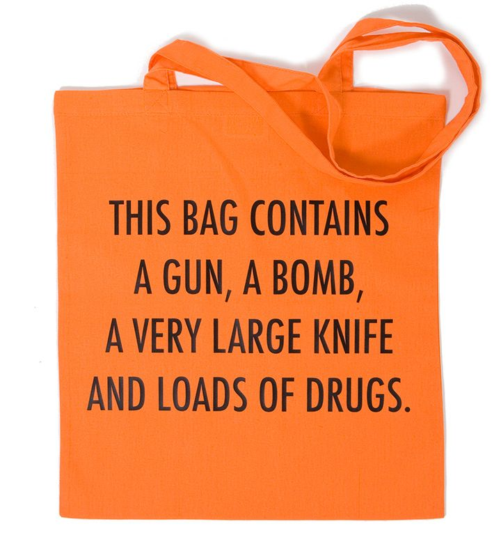 Oranje tas met opdruk 'THIS BAG CONTAINS A GUN, A BOMB, A VERY LARGE KNIFE AND LOADS OF DRUGS'.