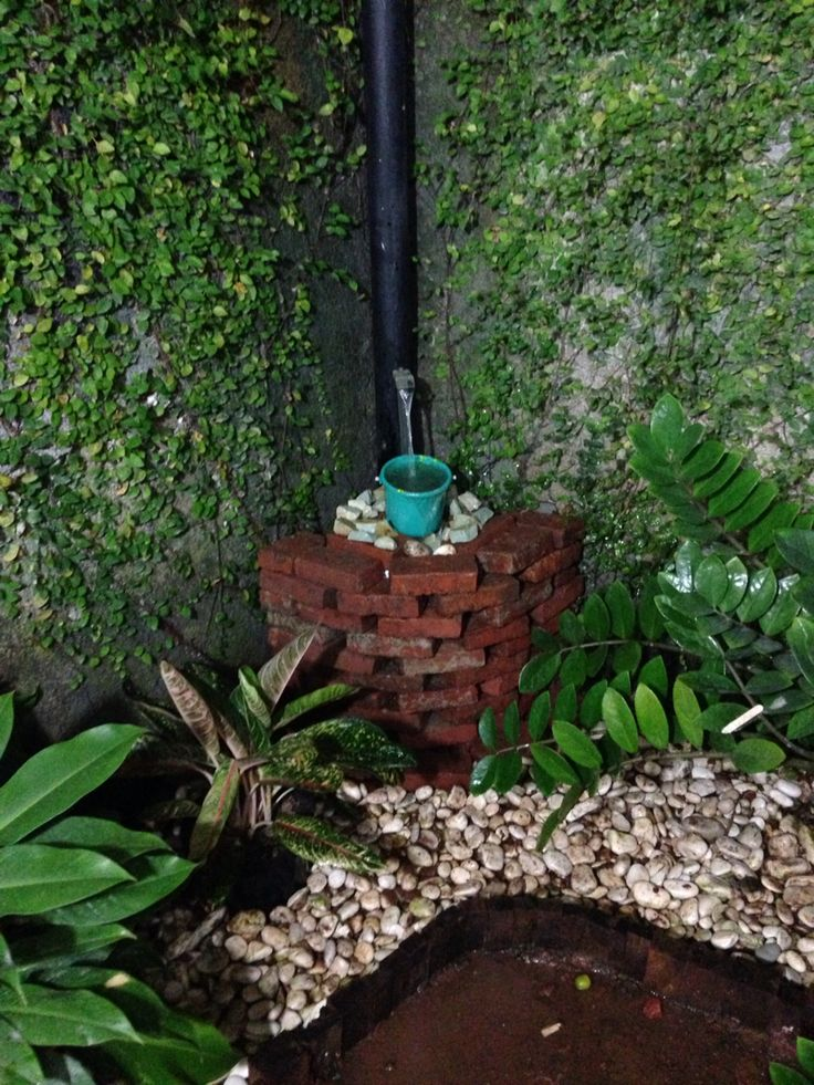 Water Feature utilize the remaining bricks, paint bucket, small stones, aquarium pump, and small bucket