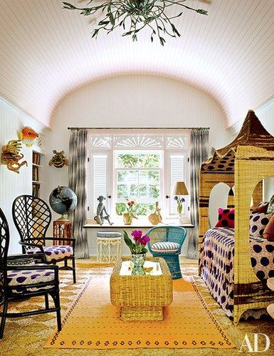 A ceiling light designed by Kemble Interiors oversees the children's playroom; the furniture is upholstered in Dutch-wax prints from AKN Fabrics, and the orange rug is from Nomadic Trading Co. | archdigest.com
