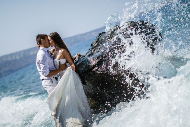 This not a photo you see often. The bride getting her wedding dress wet.  Ammoudi bay, Oia village, Santorini island, Greece - selected by www.oiamansion.com