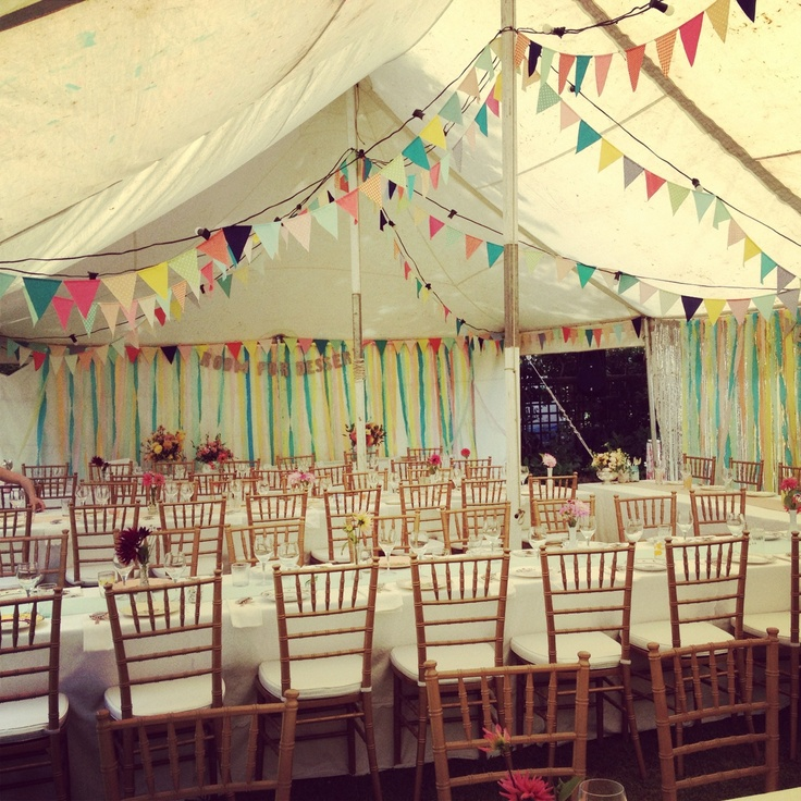 Unlined marquee with bunting and ribbon decoration. Rustic, fete style wedding or party.
