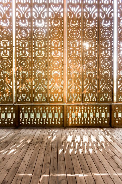 Detail shot of the ornate patterns that have been carved into the wooden screens that surround a lakeside villa in Austria.