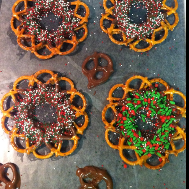 Pretzel wreaths. Dip the bottom edge in melted chocolate and around in a circle. Do an additional layer off set. Use sprinkle to decorate.