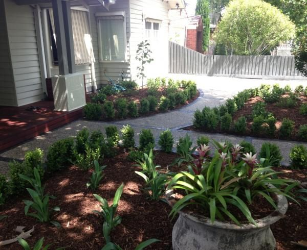 A stylish raised garden bed with new deck and exposed concrete path in Alphington.