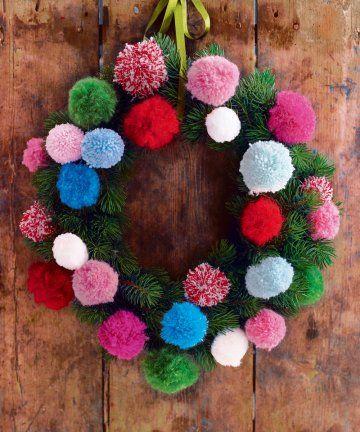 Couronne de paille recouverte de branches de sapin et de pompons en laine multicolores