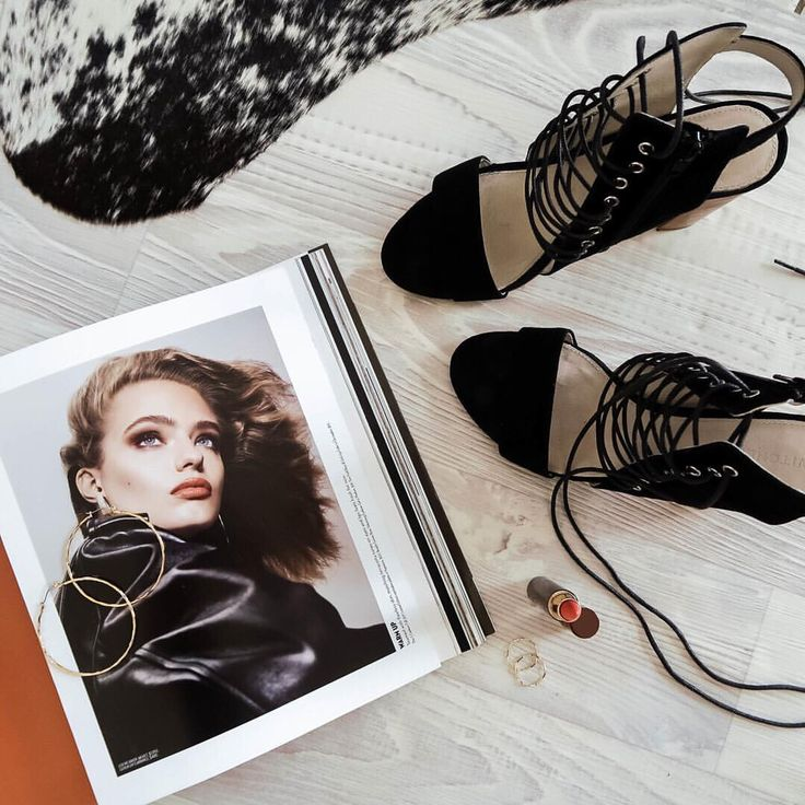 Black suede lace up block heels, gold hoop earrings, hourglass coral lipstick, magazine, cowhide rug.  Accessories @thelustlife_