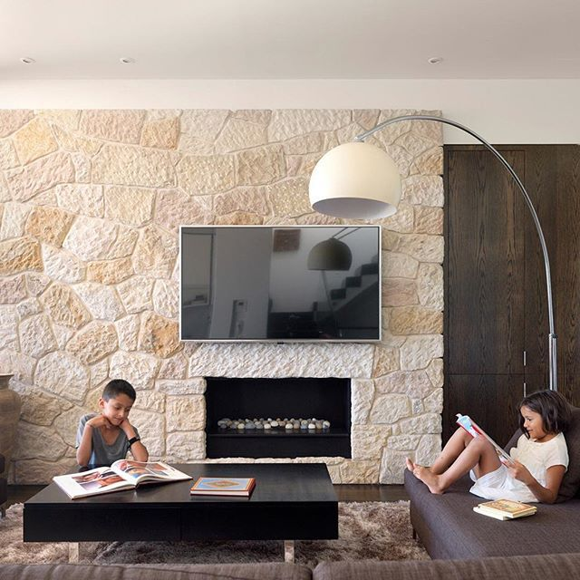 Pale sandstone cladding for the chimney breast, dark stained timber, interior designer, @decus_interiors simple yet classic furniture picks and a @realflameau #fireplace create a warm and inviting #family lounge for the #CliffTopHouse #Architecture #InstaArchitecture #Interiors #LuigiRosselliArchitect