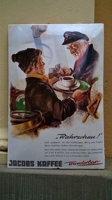Emaille reclamebord JACOBS KOFFIE - 60's - Duitsland  Zeldzaam Duitstalig emaille reclamebord van Jacobs Koffie. Uit privé collectie Nederland. Geringe gebruikerssporen geven dit bord een mooie doorleefde vintage uitstraling. Het bord is voorzien van een zeer fraaie kleurprent. Geschilderd door de toenmalige Jacobs-illustrator Ooievaar. In het onderschrift wordt op ludieke wijze de situatie geduid van de scheepsjongen die zijn kapitein koffie wil aanreiken zonder een druppel te morsen.Het…