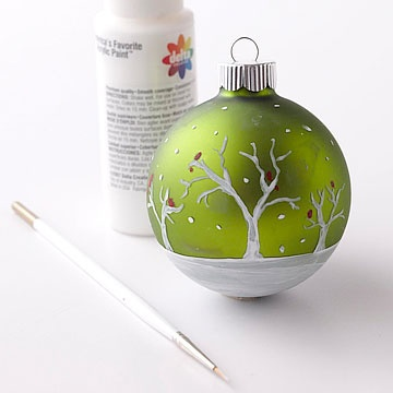 1. Paint around the bottom of an ornament with two coats of white using a #8 filbert brush. 2. Use a round brush to paint white trees in different sizes; let dry.  3. With the round brush, paint small red dashes in the trees to represent cardinals;   4. With brush bristle tips (or the brush handle dipped in paint), lightly dab white dots to represent falling snow.
