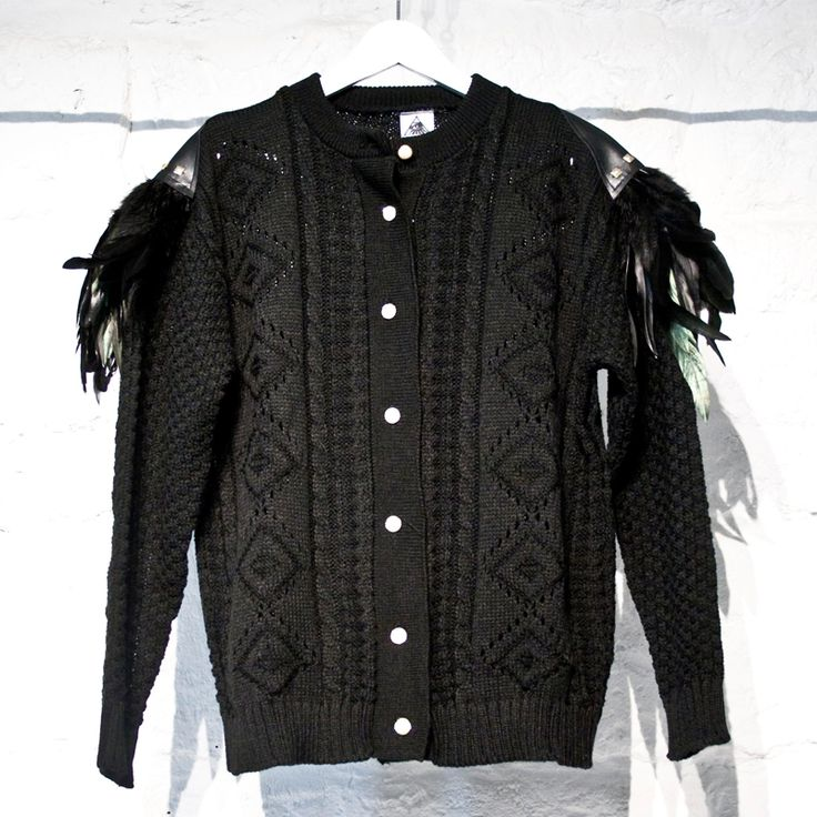 Cardigan in 100% PL di colore nero con lavorazione a maglia sul davanti, bottoni di colore oro e con perla.Piume applicate su spallina in eco-pelle decorata con borchie dorate.Taglia unica.