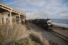 """Returning to Los Angeles, the San Diego Steam Special behind restored Santa Fe 3751, passes under the historic Coast Highway overpass in Del Mar, Calif., on June 1, 2008. The 3751 had been the last steam locomotive in passenger service on the famed """"Surf Line"""" so this event, the first since the steamer's final run in August 1954, carried an enhanced sense of history."""