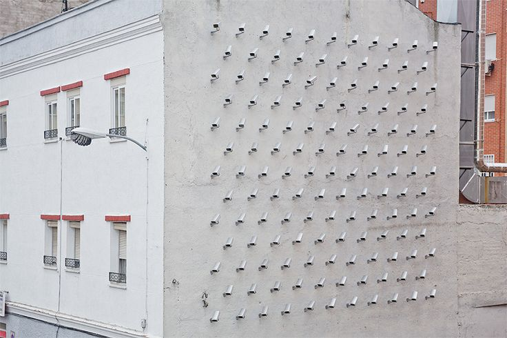 """Installed with the """"intention of not watching over anything,"""" SpY's new intervention in Madrid features 150 fake surveillance cameras on the side of a building. The Spanish street artist is known for his appropriation of urban elements to make his message known and this newest Cameras piece is no exception. http://restreet.altervista.org/spy-dissemina-le-sue-provocazioni-in-piazze-e-strade/"""