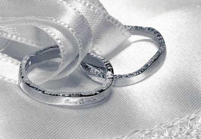 Fedi Nuziali con lavorazione artigianale sui bordi. Modello Fine oro bianco 18 kt. / 750. Superficie lucida o satinata con pavè di diamanti sul bordo per la fede femminile