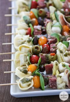 Antipasto Kabobs drizzled with Basil Pesto . {Cherry tomatoes, tortellini, olives, salami, prosciutto, cheese, basil leaves}