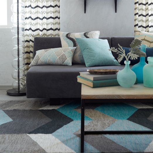 The Geo Wool Kilim is handwoven of heathered yarn that's been space-dyed, a unique twisting and dyeing technique that yields a rich multi-colored effect. This results in dramatic, oversized geo patterns with neutral hues alongside pops of teal, which bring a fun, modern feel to a room.