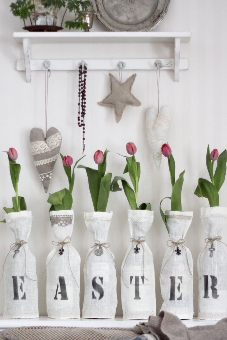 easter - wine bottles with white linen & letters printed on the fronts.  Single tulip in each bottle.