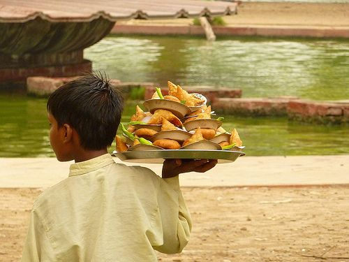 Boy trying to sell snacks at India Gate in Delhi, India.