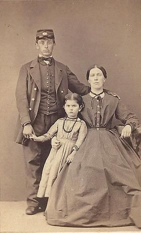 This photo is often identified as a  dead Civil War soldier and his family. This is wrong on many counts.  The man is not in a soldier's uniform, it is the uniform of a telegraph operator or train conductor.  A dead soldier sent home from the war could never look this good. He is staring straight at the camera, and he is standing alone, which we know makes it impossible for him to be dead.   For more info, click this site:   http://dealer042.wix.com/post-mortem-photos