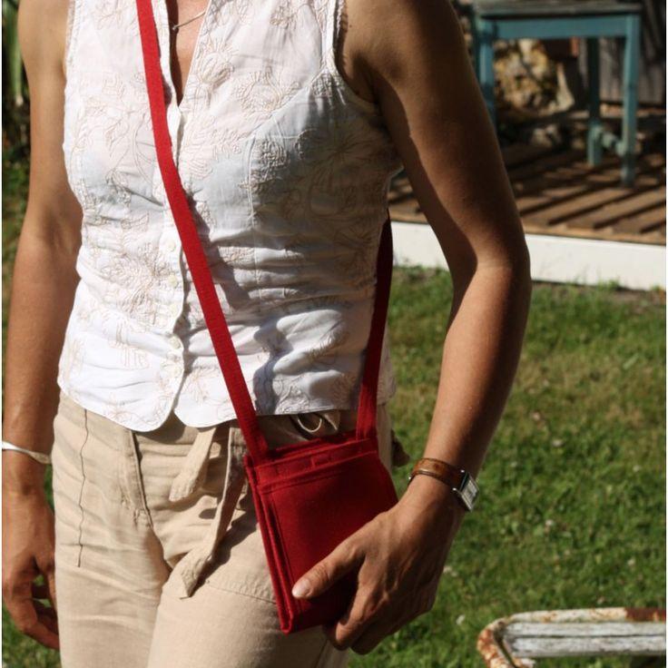 Ce Ti sac discret dans son format devient chic par son tissu intérieur et extérieur de couleur rouge Hermès. La bandoulière et le biais bordeaux offre un contraste tout en douceur.