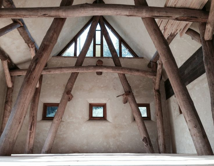 Interior Of The Timber Frame, Glazed Gables With Coloured Panes In The  Middle. Lime Render Covering The Straw Bales
