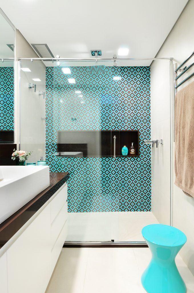 Bagno moderno con la parete della doccia rivestita in piastrelle blu turchese, motivo geometrico. Muri e pavimento in ceramica bianca.