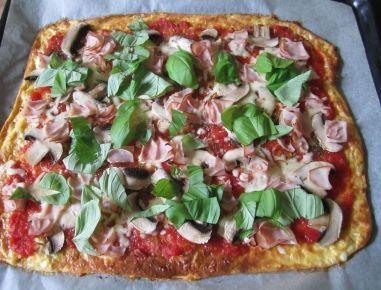 Für die Low Carb Pizza den Ofen auf 170 °C Heißluft vorheizen. Magertopfen, geriebenen Pizzakäse und Eier in einer Schüssel miteinander vermischen,