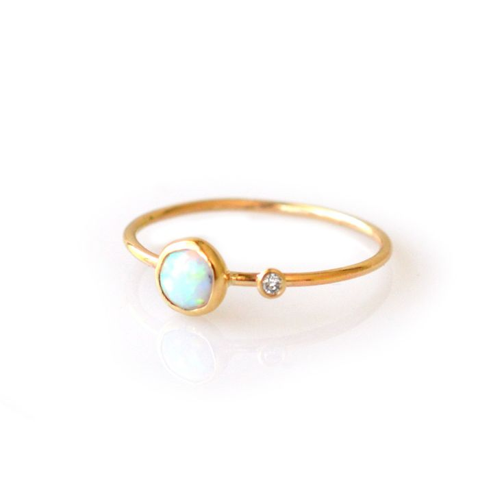 -solid 14kt gold -genuine 5m opal -1pt diamond -1mm ring band A simply gorgeous ring with a centered opal stone and a 0.25 carat diamond set off to the side. Unique and contemporary. (this ring is mad
