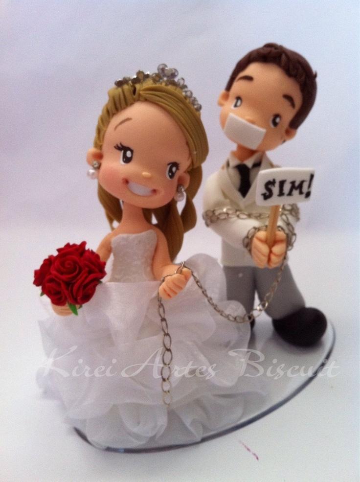 """Noivo acorrentado com plaquinhas escrito """"sim""""  e noiva puxando"""