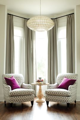 Living room, two armchairs, large chandelier, tall windows, drapes