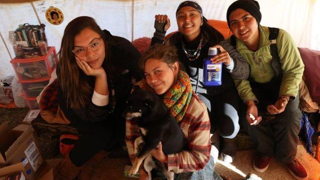 """""""Se nos unirmos teremos mais chances de vencer"""", diz Eryn Wise (à esq.), que faz parte do movimento. Integrante dos povos jicarilla apache e laguna pueblo, do Novo México (EUA). Conforme o protesto crescia, aumentavam também as tensões. Em novembro, quando manifestantes tentaram furar um bloqueio para cruzar uma ponte, foram barrados com balas de borracha, gás lacrimogênio e canhões de água. Em outro embate, seguranças privados atacaram manifestantes com cães."""
