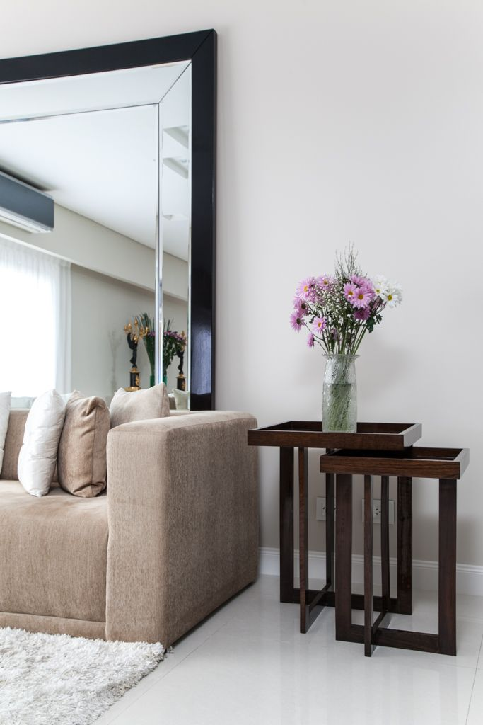 Detalle de mesas encastradas, sillón, alfombra y espejo de pie con diseño de biseles.