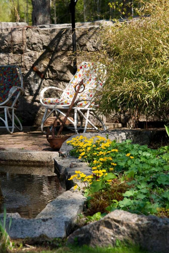 """""""Jag är nöjd med helheten i min trädgård med sten, glittrande vattenblänk, rostigt järn, snickarglädje och blommor. Något av det bästa i trädgården är dammen där vattnet kommer ur den stora stenen"""", tycker hon. """"Vatten och sten skapar en lugn och ro i trädgården med det porlande ljudet och behagliga kontraster. Trädgårdsmöblerna i järn och trä är valda med omsorg och smälter in i den lummiga atmosfären. Hit är inga plastmöbler välkomna."""""""