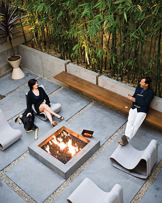 beautiful courtyard using simple, large concrete slabs warmed up with pea gravel, a fire pit, a rich wood bench, and a bamboo planter for screening