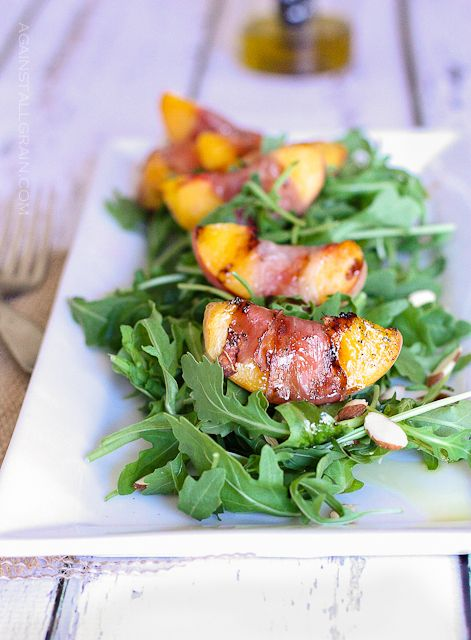 Grilled Prosciutto Peach Salad: 2 ripe yellow peaches, pitted and cut into 12 slices; 12 thin slices of prosciutto; 6 cups baby arugula; 2 tablespoons slivered almonds; 2 tablespoons extra virgin olive oil; 1 tablespoon balsamic vinegar; salt and pepper