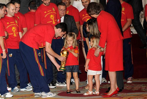 Princess Leonor Photos - Princess Leonor of Spain touches the trophy held by goalkeeper and captain Iker Casillas, watched by Princess Sofia, Princess Letizia and Queen Sofia of Spain while the FIFA 2010 World Cup winning team Spain are received by the Spanish royal family at Zarzuela Palace on July 12, 2010 in Madrid, Spain. - Spanish King Meets FIFA 2010 World Cup Winning Team
