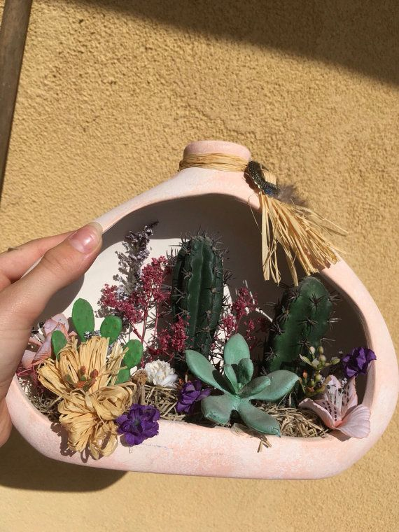 This is a gorgeous Ceramic Faux Cacti and Succulent filled terrarium. It features a beautiful array of succulents with some other floral decor, a bolo tie on top and a feather adornment. This will make a beautiful Southwestern Cacti Decor piece or an awesome ️VINTAGE gift for te Cctus Liver.  It measures 7.25 tall and 10 wide. Signed Jason to Mom and Dad 98, 99. That could easily be painted over or left as it is,