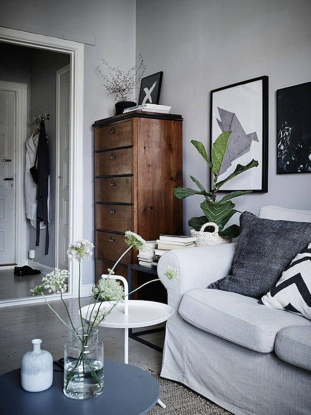 A tallboy in the sitting room of a calm, cocoon-like Swedish space in greys. Stadshem.