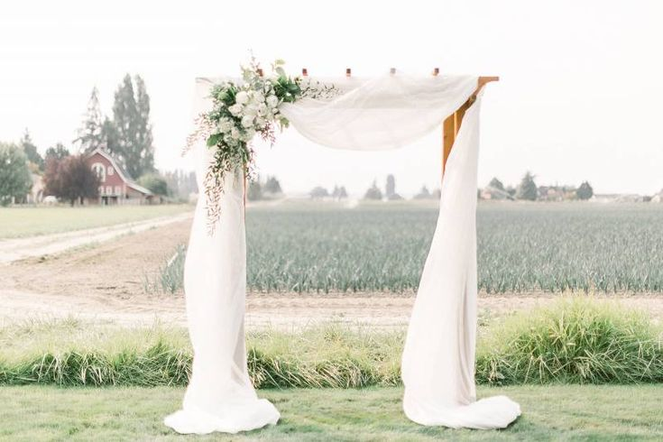 Modern Rustic Chic White Wedding Ceremony arbor with white drape and floral arrangements