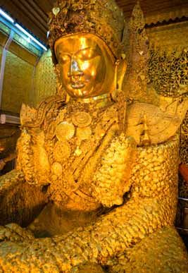 The Mahamuni Buddha in Mandalay. Followers travel here and lay gold leaves upon the Buddha. So many gold leaves have been laid upon the Buddha that the original shape is distorted because of the thick layers of gold added to it. The Temple is open to visitors, but women are not allowed to approach the Buddha instead that are asked to put their gold leaf in the donation box.