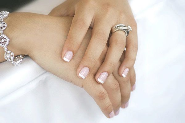Classic French manicure for a traditional bride on her wedding day.