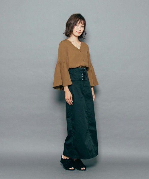 茶色のブラウスにグリーンのスカートを合わせて黒いミュールを履いた女性