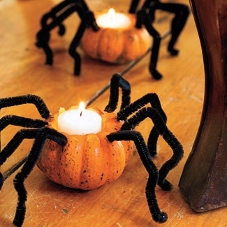 Halloween Creepy Crawlers  Scooped-out mini pumpkins become spidery votives, thanks to tealights and pipe cleaners