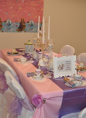 Royal tea party setup with linens and chair covers, candlesticks and fine china