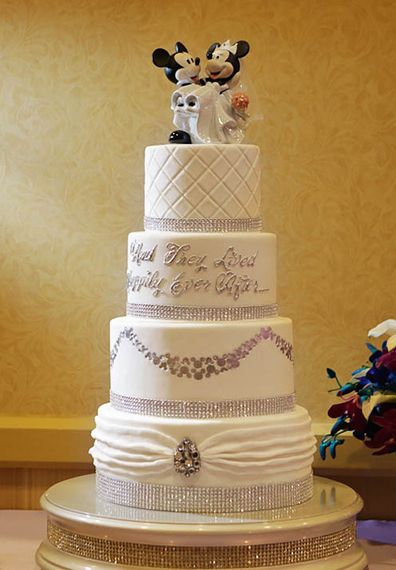 Mickey and Minnie are the finishing touch on this four tier wedding cake.