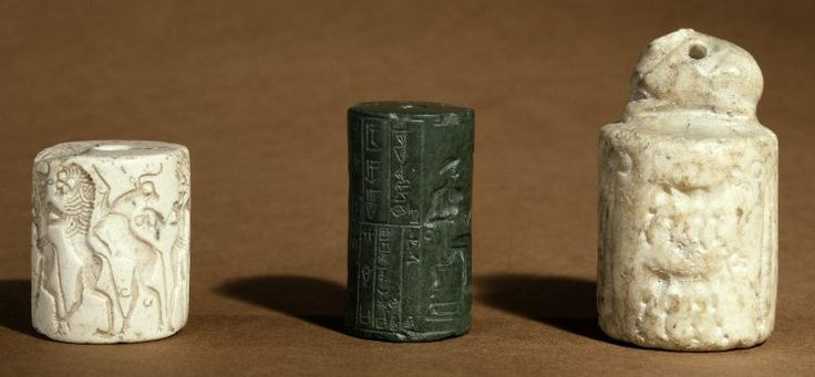 Aragonite cylinder seal; contest scene; in the centre -  a bearded, nude hero, with a crested head-dress, holds a bull in each hand (possibly to protect them); to the left - bull-man (in profile) fights rampant lion. A bird in between them; to the right - the bull-man, full faced, fights two lions; an ibex or small goat between them. Terminal an ibex head; slightly chipped at edges.  Greenstone cylinder seal; a goddess wearing a striped robe and a multiple-horned head-dress stands with both…