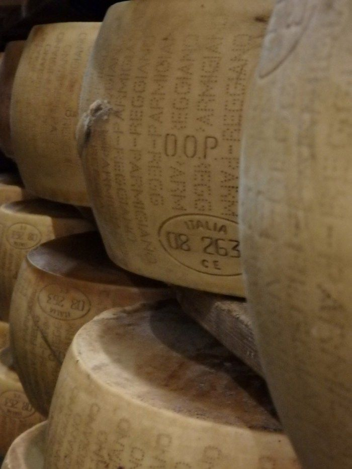 wheels of Parmigiano Reggiano on the aging shelves, seen on the Italian Days Food Tour