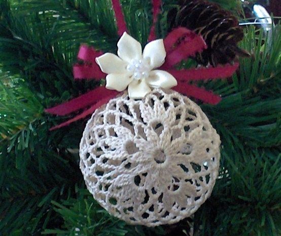 """Crochet Ornament : flower pattern on both sides, with the rest of ornament in a mesh pattern. Burgundy color ribbon bow and hanger, with Ivory color flower hot glued to the top. Stiffened with """"Stiffy"""" fabric stiffner. Measures approximately 3"""" high, by 3"""" wide, 8 1/2"""" circumference"""