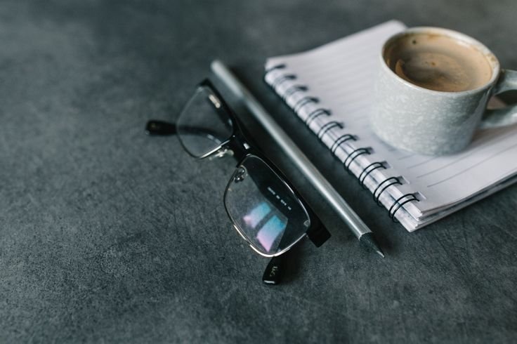 Black glasses, silver pencil, opened notepad and cup of cofee